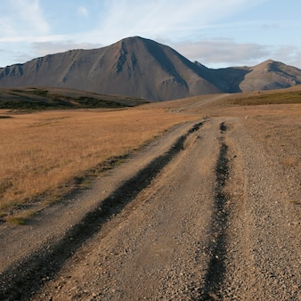Ruts in dirt road leading to mountain