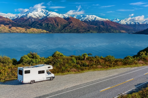 An rv next to lake wanaka viewpoint with snow capped mountains in the distance