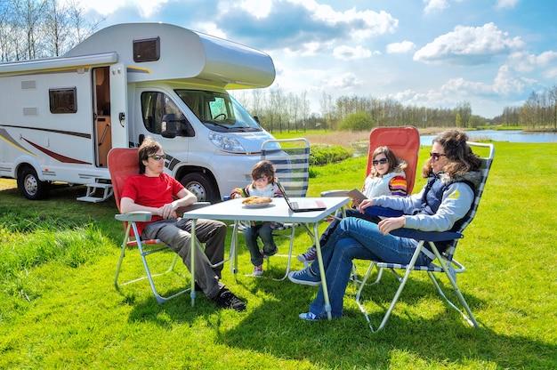 家族での休暇、rv(キャンピングカー)は子供と一緒に旅行、子供と幸せな親はキャンピングカーでの休日の旅行でキャンプのテーブルに座る