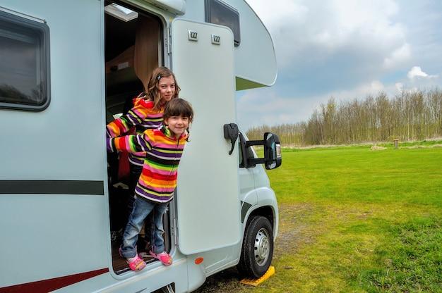 キャンピングカー(rv)の子供たちは、休暇でキャンピングカーで家族旅行