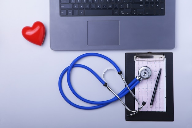 Рабочее место врача с ноутбуком, стетоскоп, рецепт rx и красное сердце на белом столе.