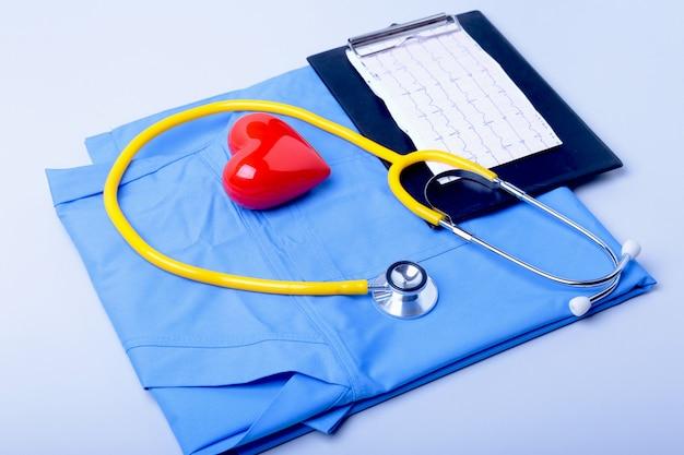 Медицинский стетоскоп, список истории болезни пациента, рецепт rx, красное сердце и синий доктор униформа крупным планом