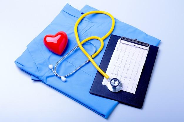 Медицинский стетоскоп, терпеливый список истории болезни, рецепт rx, красное сердце и синий крупный план униформы доктора.
