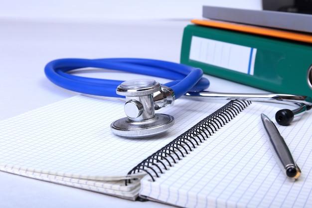 机の上のフォルダーファイル、聴診器、rx処方。背景をぼかし。