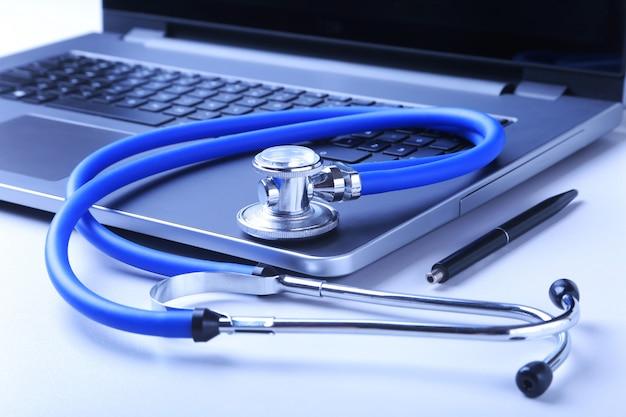 Рабочее место врача с ноутбуком, стетоскоп и рецепт rx на белом столе