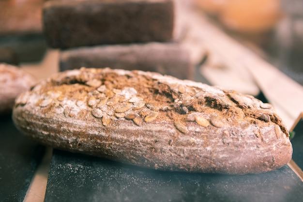 ライ麦バゲット。居心地の良いフランスのパン屋に横たわっているヒマワリの種とおいしいライ麦バゲットのクローズアップ