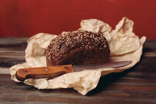 木製のテーブルと鋭いナイフを包装する紙の上で焼くライ麦パン