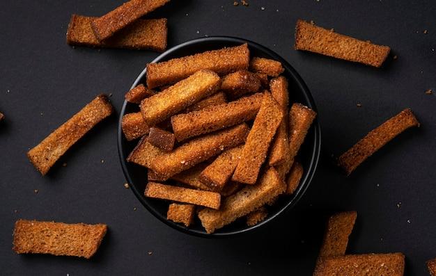 Гренки из ржаного хлеба, соленые хрустящие хлебные палочки на черном фоне с копией пространства