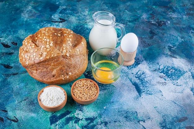 Rye bread, egg yolk, egg and milk on blue surface.
