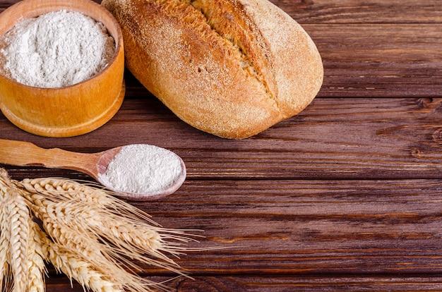 Ржаной хлеб, мука и колоски на деревянном фоне.