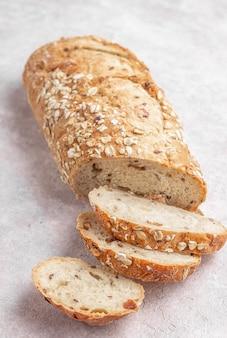 Буханка ржаного хлеба с семенами, изюмом и мюсли. концепция здорового питания. итальянский хлеб la pagnotta на светло-бежевом фоне. выборочный фокус