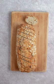 Буханка ржаного хлеба с семенами, изюмом и мюсли. концепция здорового питания. итальянский хлеб la pagnotta на светло-бежевом фоне. вид сверху