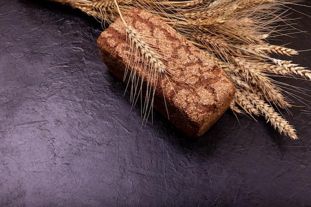 어두운 배경에 호밀 빵 바삭한 빵 껍질과 소박한 사워도 빵