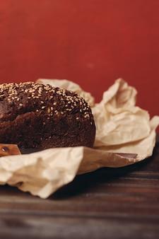 Ржаной хлеб на бумажной упаковке на красном фоне и деревянный стол с острым ножом. фото высокого качества