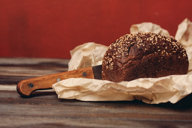 Rye bread on paper packaging on a red and a wooden table with a sharp knife