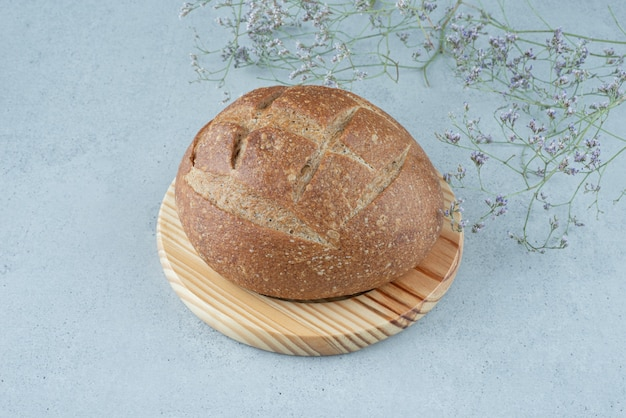 식물을 가진 나무 보드에 호밀 빵 롤
