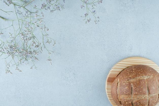 Rotolo di pane di segale su tavola di legno con pianta