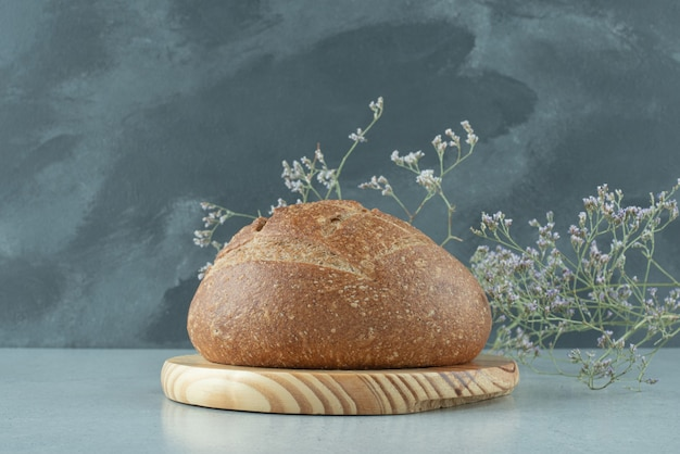 Rye bread roll on wooden board with plant