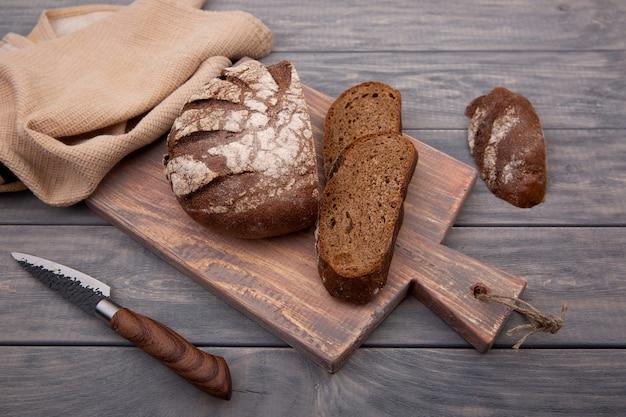 素朴な木で作られたナイフで木の板に細かく切ったライ麦パンの丸いパン。上面図。