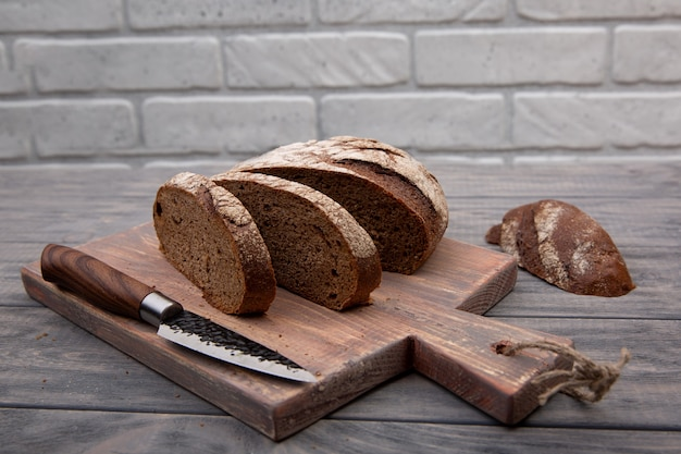 素朴な木で作られたナイフで木の板に細かく切ったライ麦パンの丸いパン。