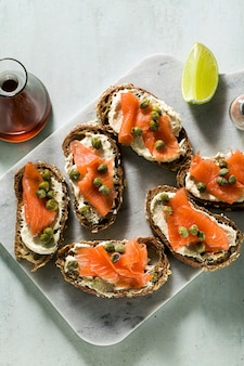 Rye bread sandwiches with smoked salmonnd capers on marble board and sesame oil with slices of lime