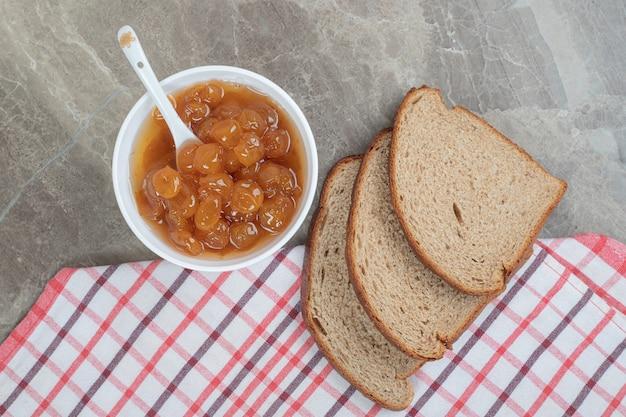 テーブルクロスと大理石の表面にライ麦パンのスライスとベリージャム。高品質の写真