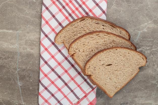 大理石の表面にライ麦パンのスライスとテーブルクロス。高品質の写真