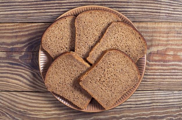 나무 테이블에 접시에 호밀 빵 조각, 상위 뷰