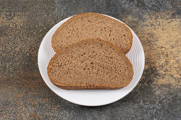 하얀 접시에 호밀 빵 조각입니다.