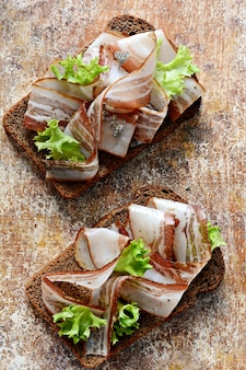 Rye bread toast with slices of bacon (pancetta, lard), garlic and italian herbs, antipasti, italian bruschetta (crostini)