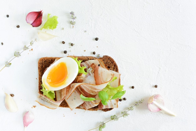 Rye bread toast with slices of bacon (pancetta, lard), soft-boiled egg, garlic and italian herbs.