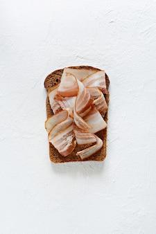 Тост из ржаного хлеба с кусочками бекона (панчетта, сало), чесноком и итальянскими травами, закусками, итальянской брускеттой (кростини)