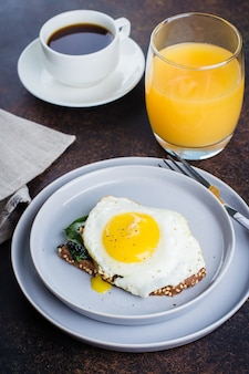 Rye bread toasts with fried spinach and egg. healthy breakfast food concept.