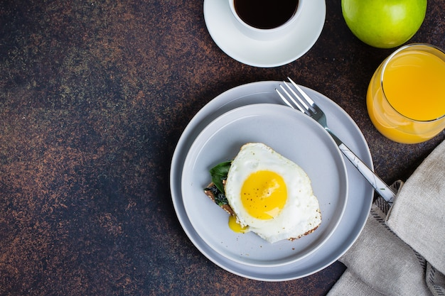 Rye bread toasts with fried spinach and egg. healthy breakfast food concept