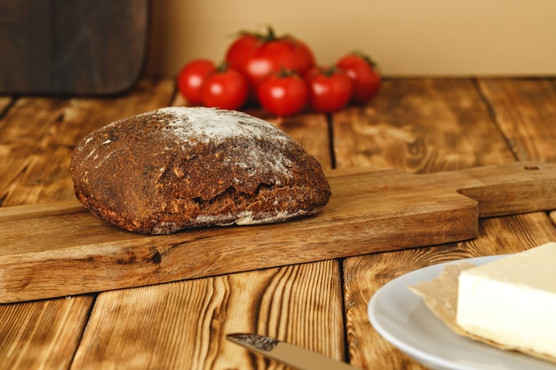 Rye bread with flour on top on cutting board on wooden table