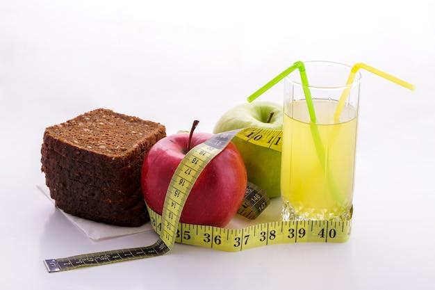 Ржаной хлеб с зелеными и красными яблоками и соком в стакане на белой тарелке с желтой меркой ...