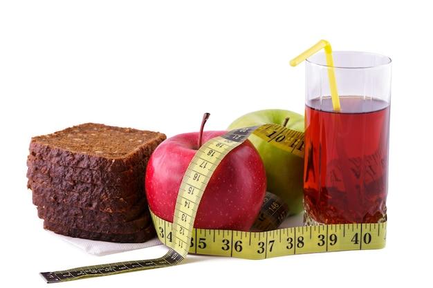 Ржаной хлеб с зелеными и красными яблоками и соком в стакане на белой тарелке с желтой измерительной лентой