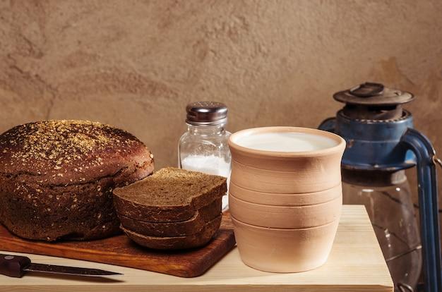 도마에 소금을 넣은 호밀 빵, 우유가 든 도자기 냄비, 등유 랜턴. 소박한 스타일의 정물
