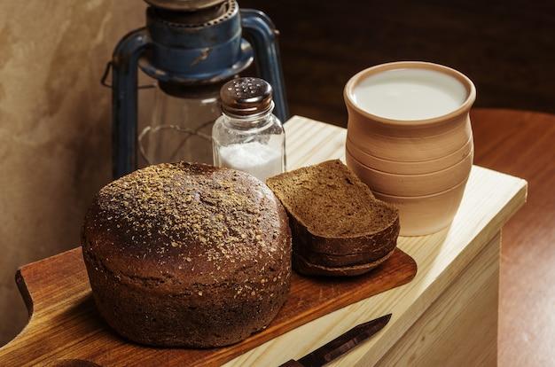도마에 소금을 넣은 호밀 빵, 우유가 든 세라믹 냄비. 소박한 스타일의 정물
