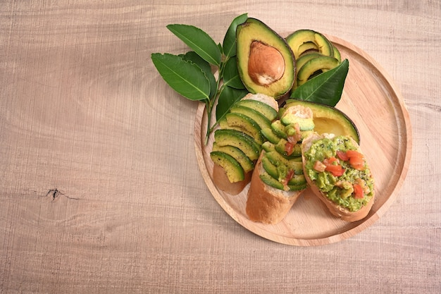 Rye bread with sliced avocado on wooden plate for healthy breakfast.