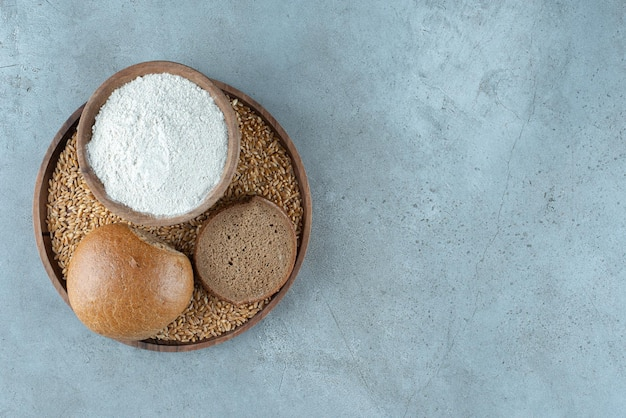 Rye bun with bowl of flour on wooden plate.