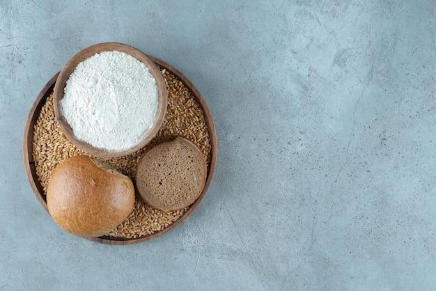 Ржаная булочка с миской муки на деревянной тарелке.