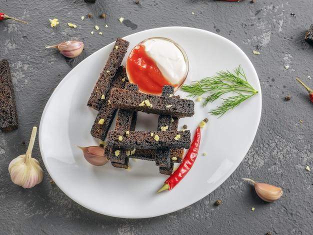 Ржаные хрустящие гренки или закуски с чесноком и острым красным перцем и соусом в белой тарелке на сером бетонном фоне