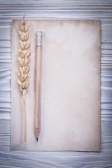 Ржаные уши, чистый старинный лист бумаги и карандаш на деревянной доске