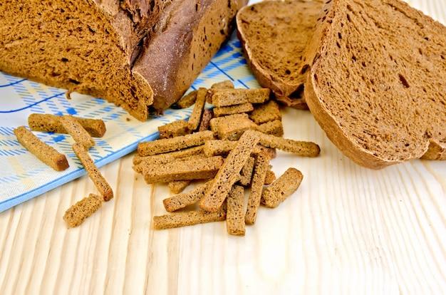 Ржаной домашний хлеб, крекеры, синяя ткань на фоне деревянных досок