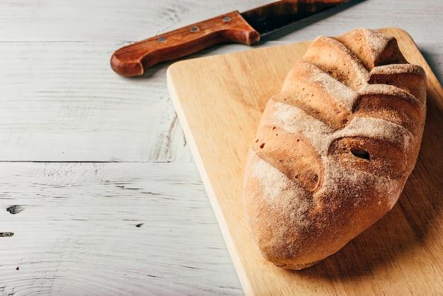 Ржаной хлеб на разделочной доске с ножом.