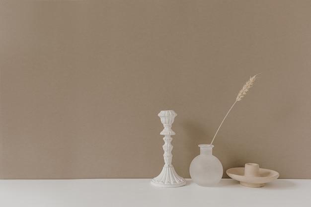 花瓶のライ麦または小麦の耳の茎、ニュートラルなパステルベージュの壁の背景に白いテーブルの上に立っているキャンドルスティック。