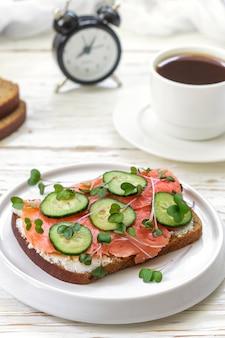 Rye sandwich with salmon, cucumber, cheese cream and micro greens