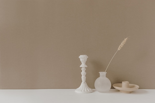Rye or wheat ear stalk in vase, candle stick standing on white table against neutral pastel beige wall background.
