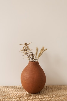 Rye, wheat stalks bouquet in red clay pot on white wall. minimal decorated interior design
